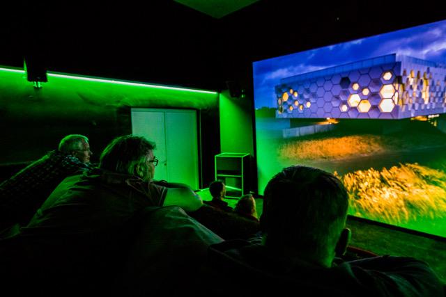 Een kijkje over de schouder van een bezoeker, het wordt avond en de Grutto daalt neer in het Afsluitdijk Wadden Center.