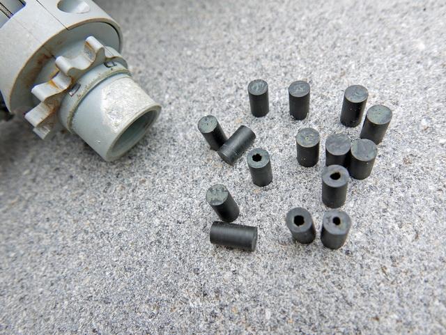 Op de plastic as is duidelijk de overmatige slijtage te zien. Daarnaast afgebeeld de rollagers waarvan sommige hol zijn en zodoende makkelijk in kleine stukken kunnen breken.
